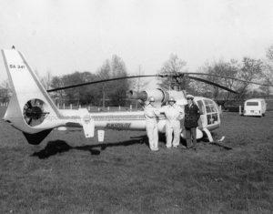 Na even in de lucht geweest te zijn staat de Westland Gazelle bij de sportvelden van de AVD weer op de grond. Op deze foto poseert een opperwachtmeester van de AVD bij de heli, samen met twee technisch medewerkers die voor de brandstof zorgden.